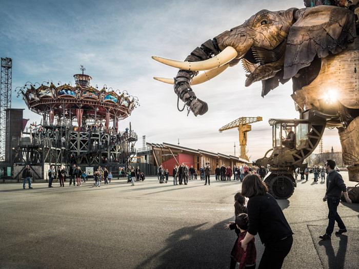 The elephant of Les Machines de l'île tours around the warehouse buildings of l'Île de Nantes. Photo Credit: Franck Tomps/LVAN