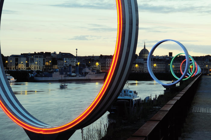 Daniel Buren's work, titled Les Anneaux and part of the Estuaire collection, frames views across to the historic centre of Nantes from the island. Photo Credit: Bernard Renoux/LVAN, Estuaire 2007