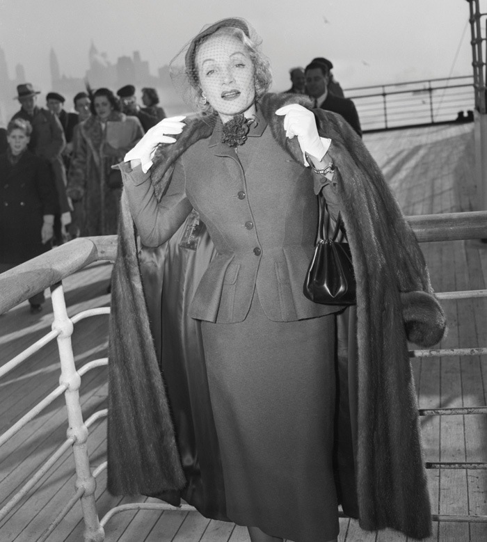 Marlene Dietrich wearing a day suit by Christian Dior on board the Queen Elizabeth arriving in New York, 21 December 1950. Image Credit: Getty Images
