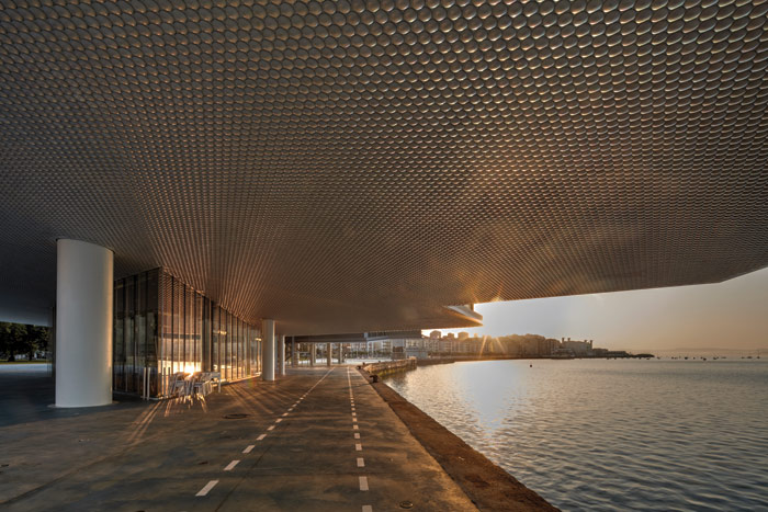 The rising sun sandwiched and reflected by the Centro Botín's porcelain undersides and the water, on a day that's not rainy
