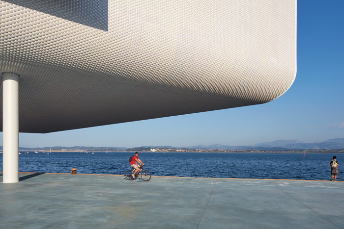 The building cantilevers into the Bay of Santander, and the waterside becomes public realm