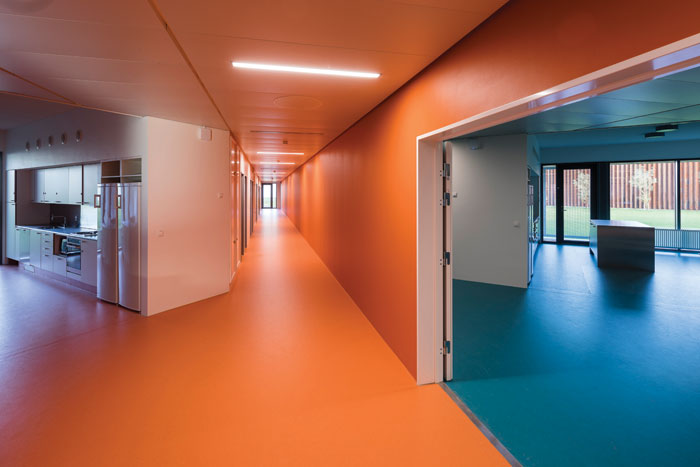 Each housing unit, saturated with a single colour, includes four to seven cells off a corridor, along with a communal kitchen and leisure space. Photo Credit: Torben Eskerod