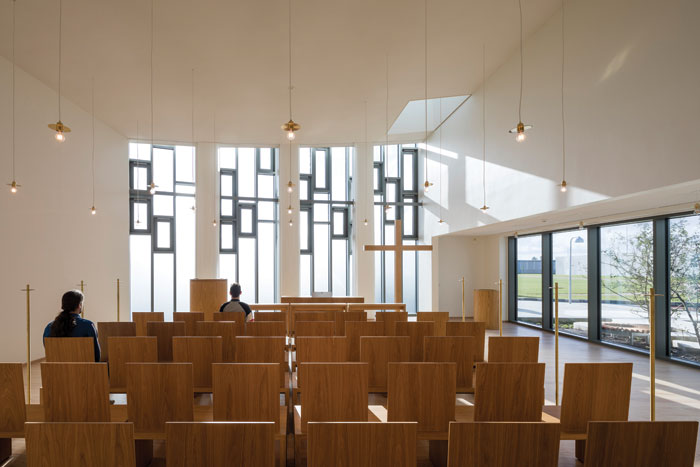 The church in the activity house is flooded with light and features oak and brass furnishings. Photo Credit: Torben Eskerod