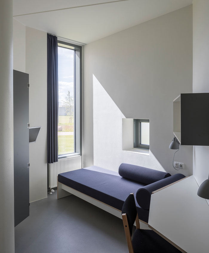 The sleek and bright cell design includes a 3.1m-tall barless window and an en-suite bathroom clad in blue ceramic tiles. Photo Credit: Torben Eskerod