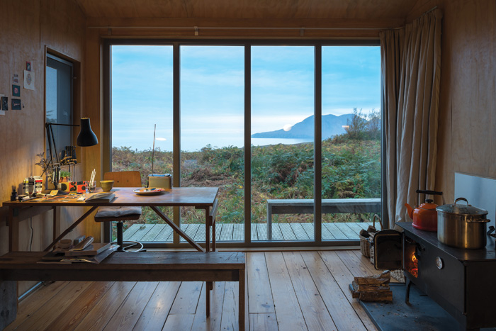At Sweeney Bothy, its mono-pitched form accommodates a platform bed in the roof and the west-facing elevation is entirely glazed. Photo Credit: Johnny Barrington