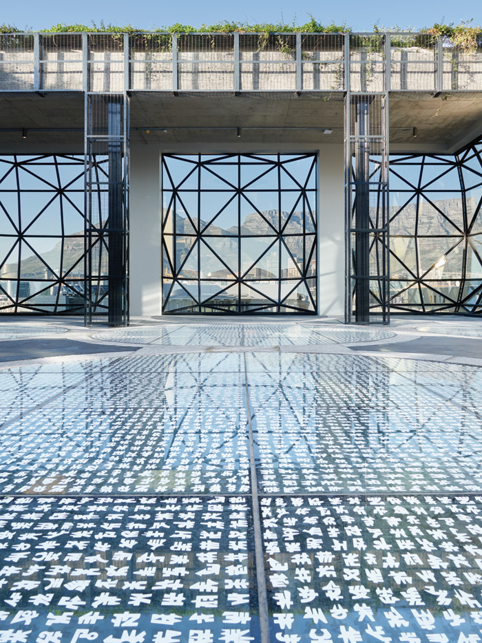 The rooftop Sculpture Garden has a glass floor which allows light into the atrium and is decorated with a fritting based on the work of artist El Loko. Photo Credit: Mark Williams