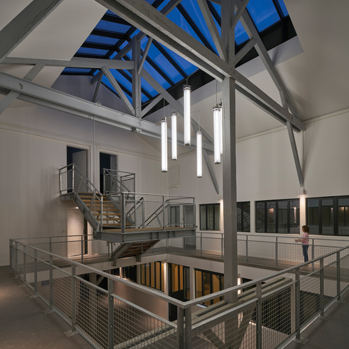Natural daylight and social spaces are offered by the printshop's central atrium. Photo Credit: Didier Boy De La Tour