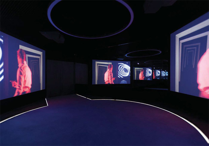 Two views of the Lair showing footage of classic Bond movies through the decades. Image Credit: Kristopher Grunert