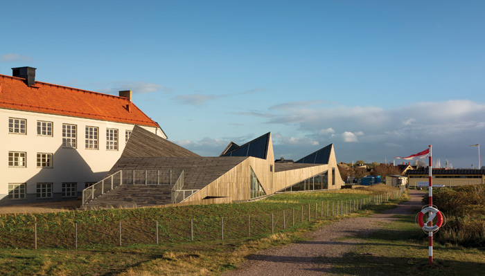 The sculptural Råå Preschool (2013), along the Swedish Öresund coast, uses hardy Robinia wood. Image Credit: Adam Mørk