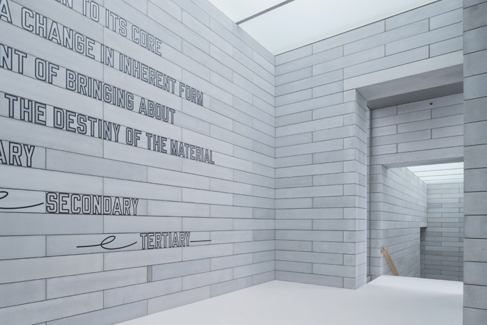 A wall text artwork by Lawrence Weiner, specially adapted for Glenstone, welcomes visitors in the entrance pavilion. Image Credit: Iwan Baan, Courtesy Of Thomas Phifer and Partners