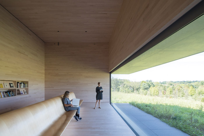 The viewing gallery, Room 7, breaks with the concrete aesthetic with its white maple interior finish. A long bench, designed by Murtin Puryear and Michael Hurwitz, invites visitors to sit and contemplate the landscape. Image Credit: Iwan Baan, Courtesy Of Thomas Phifer and Partners