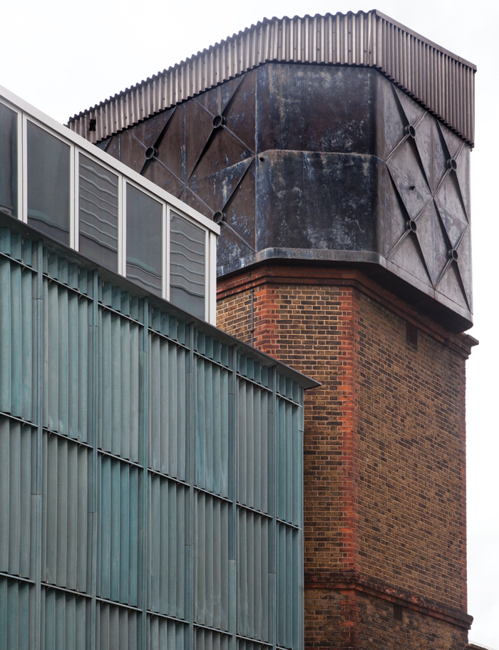 The CCA's exterior is a celebration of materiality, from the original bathhouse's brickwork and cast iron to Assemble's marine-hued corrugated fibre cement. Image Credit: Assemble