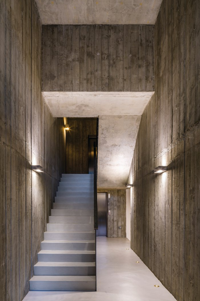 A spacious, double-height lobby with shuttered concrete walls is a conscious break from standard 'poky' entrances. Image Credit: Gareth Gardner