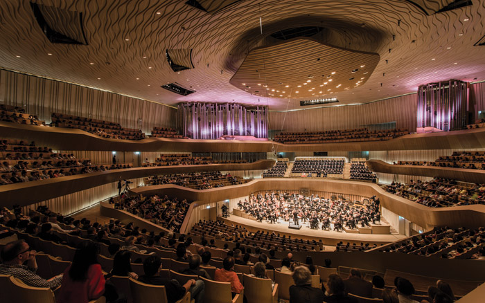 The Concert Hall, hosting two clusters of organ pipes and a 22-tonne acoustic canopy, follows the 'vineyard' seating arrangement, which surrounds the performers with audience on all side. Image Credit: Iwan Baan