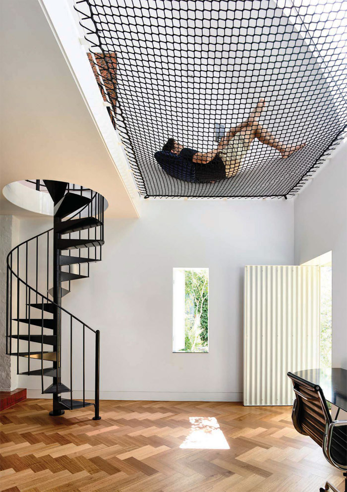 In the existing stable, now the parent's retreat, a heavyweight net fills the void between the bedroom and lower level, doing away with the need for a balustrade while providing a novel place to relax. Image Credit: Derek Swalwell