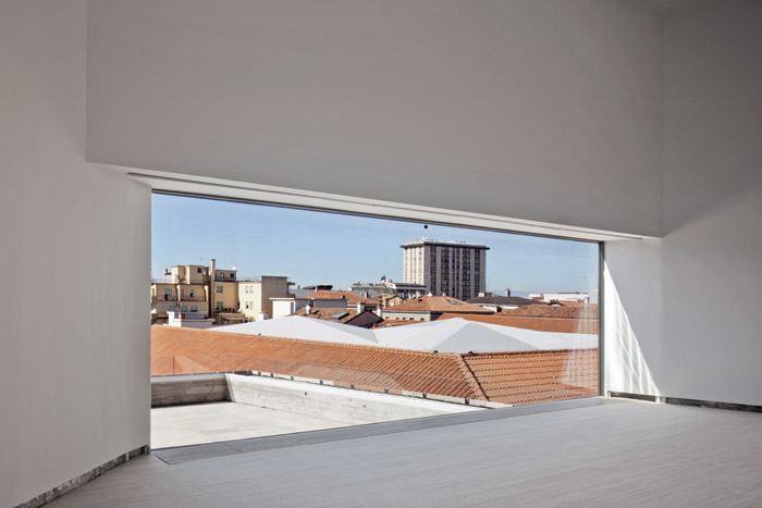 A large picture window at the very top of the building offers views out to the surrounding rooftops