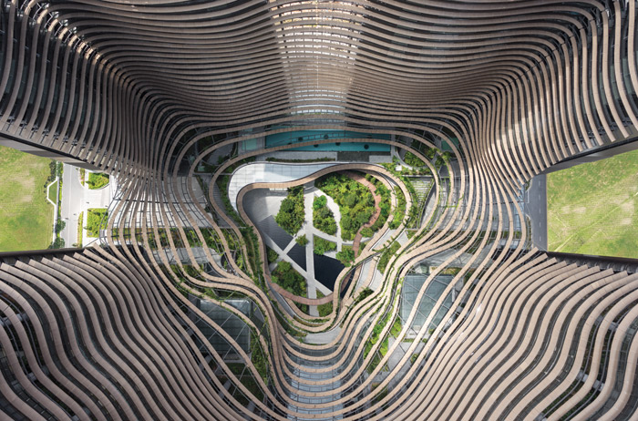 Horizontal louvres curve over the gardens of the ground floor and levels 3 and 4, then hug the contours of the office towers. Image Credit: Ingenhoven Architects / HG Esch