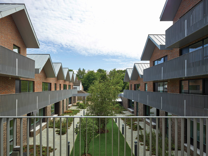 The zig-zag of the zinc-clad pitched roofs gives the illusion of terraced housing. Image Credit: Tim Soar