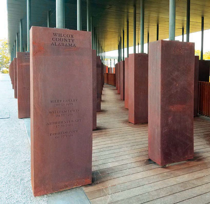 Eight hundred 1.8m-long rectangular corten steel monuments hang from the roof of the memorial square, one for every American county where a lynching took place. Each one bears the victims' names. Image Credit: Adina Solomon