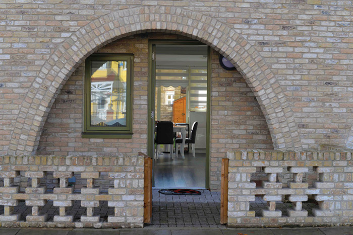 The townhouses' arches provide recesses for each front door, creating what the architect calls a 'social threshold'