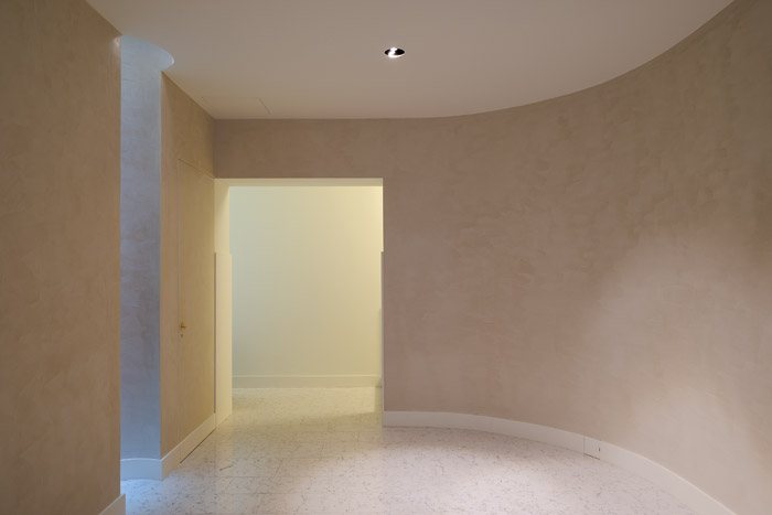 Stairs to the basement lead to a clean, minimalist central hallway. Image Credit: DMF