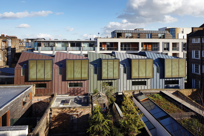The upper storeys of the Godson Street homes are individually wrapped in differently hued, prepatinated zinc. Image Credit: Jack Hobhouse