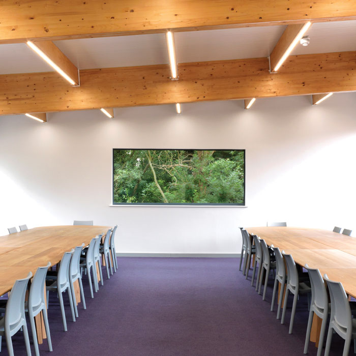 The first-floor reading room overlooks mature woodland, helping create a serene study space