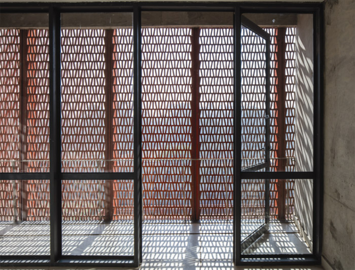 The accommodation blocks for male students are clad with red perforated screens in GRC — a direct reference to traditional Indian jali screens. Image Credit:  Christian Richters