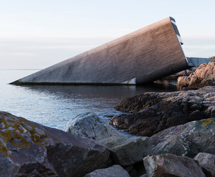 Despite the concrete almost blending in with the rocky shore, on first glance the project looks as if a building has fallen into the sea. Credit: Inger Marie Grini / Bo Bedre Norge