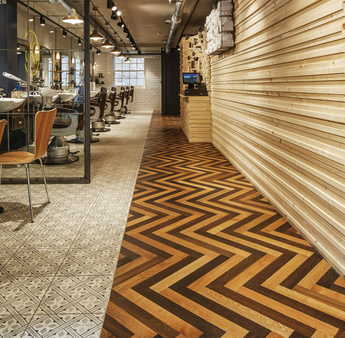range colours of engineered oak wood herringbone flooring to create a masculine vibe for Cutter's Yard barber and coffee shop Flooring: Havwoods Italian Collection. Image Credit: Havwoods Italian Collection