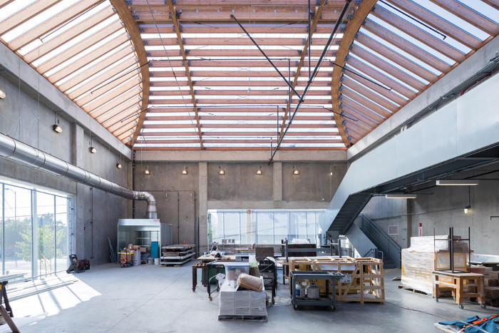 Glulam beams span the vast ceilings of studios in the new extension. Image credit: Iwan Baan.