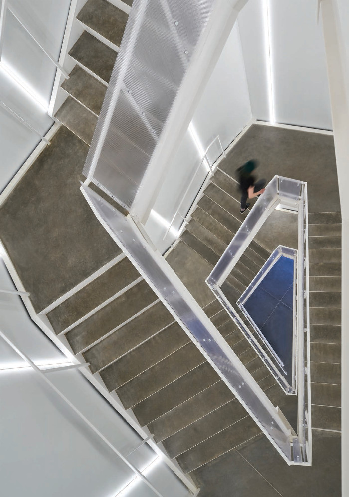 The central staircase, where necessary circulation and access doubles as a space for viewing art, illuminated by vertical LED lights. Image credit: Scott Mcdonald / Gray City Studios