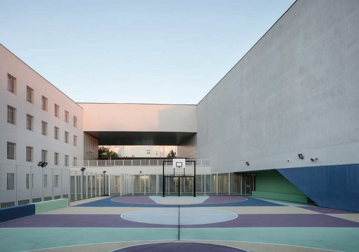 The outdoor tarmac exercise pitch, with views out to the town through the facade opening, boasts a palette of blue, green, beige and purple. Image credit: Cyrille Weiner.