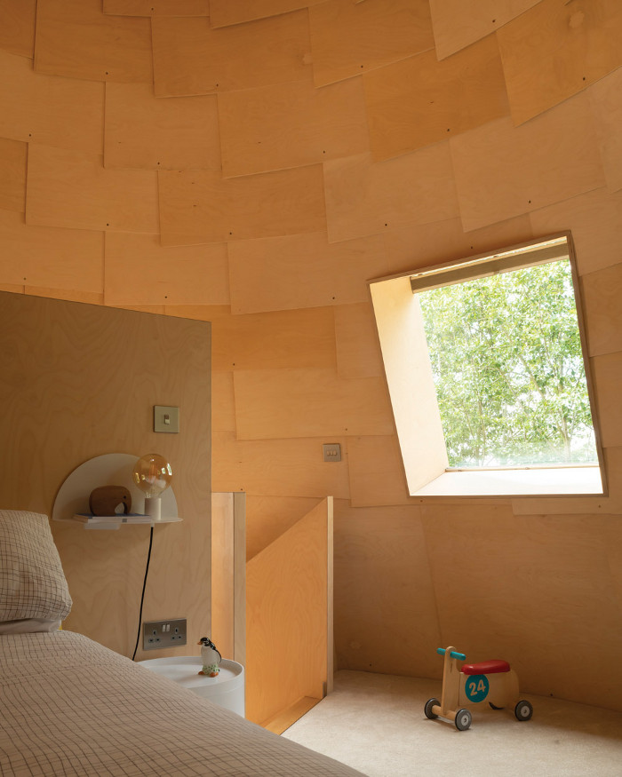 The children's bedrooms are accessed via a helical staircase made of curving plywood; inside, the cone-shaped roofs are clad in overlapping wood shingles. Image credit: Jim Stephenson