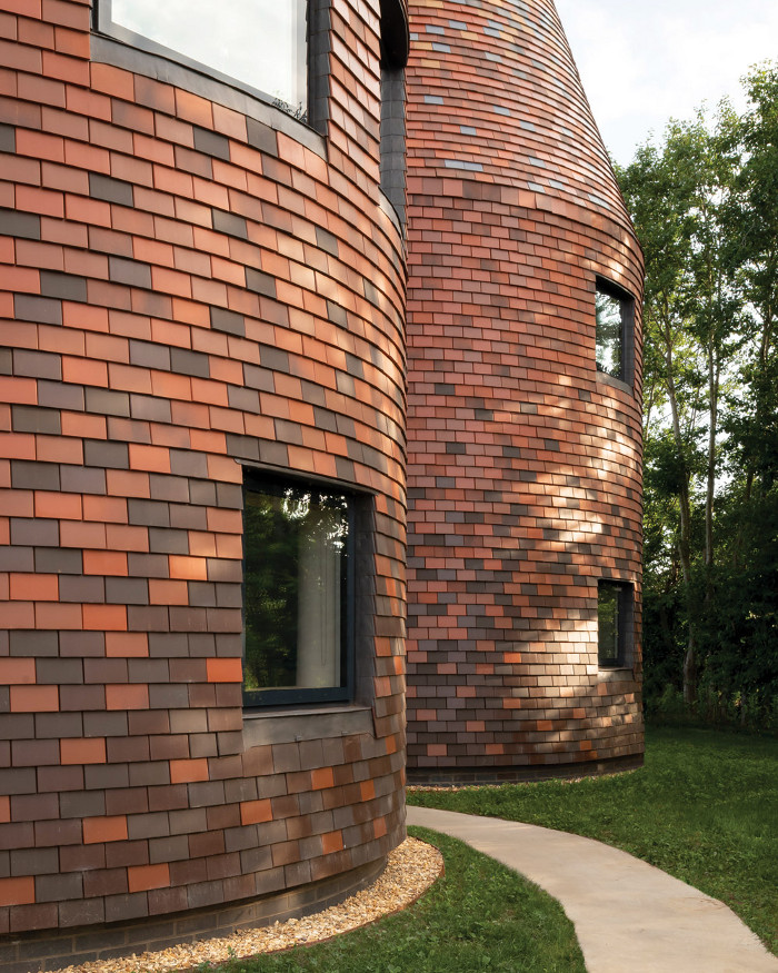 The house comprises five tower volumes, all clad in randomly patterned clay tiles giving a pixellated visual effect. Image credit: Jim Stephenson