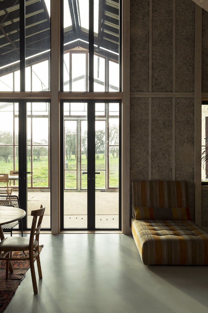 The double-height living area and large, glazed conservatory create a spatial generosity. Image credit: Oskar Proctor