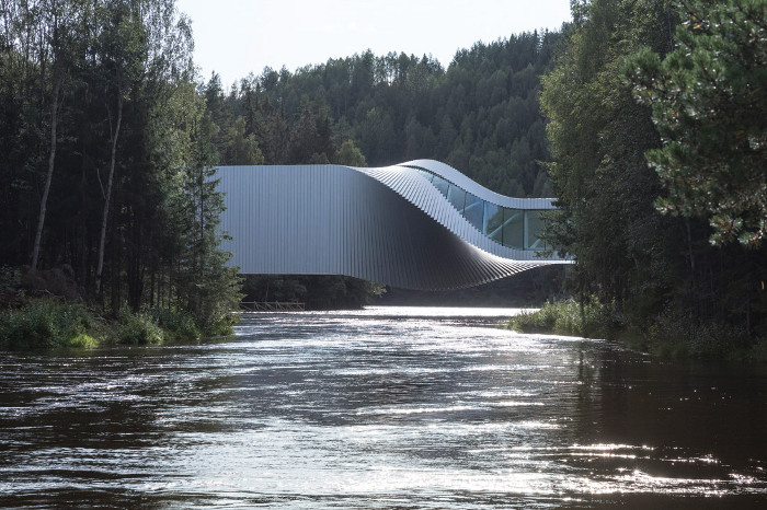 Both a building and a bridge, the project spans a river in a dramatic twist. Image credit: Laurian Ghinitoiu.