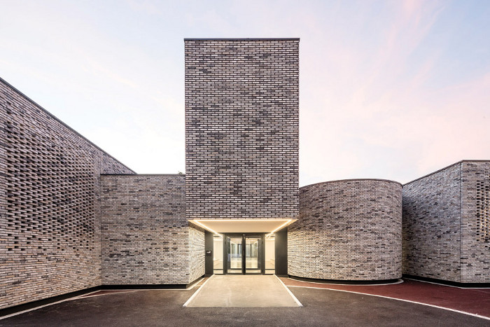 The facade uses slim Wienerberger bricks in muted tones of pale grey