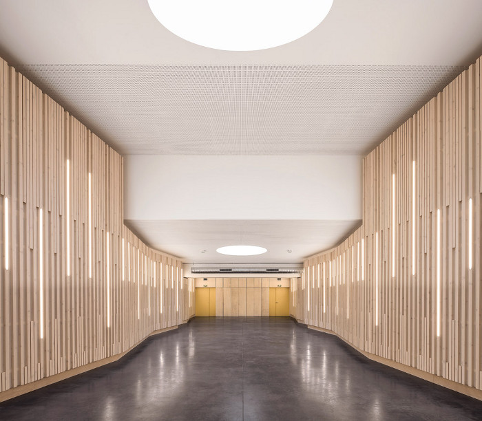 The school's auditorium has the highest ceiling of all the rooms. It features undulating walls of vertical wooden panelling to control acoustics