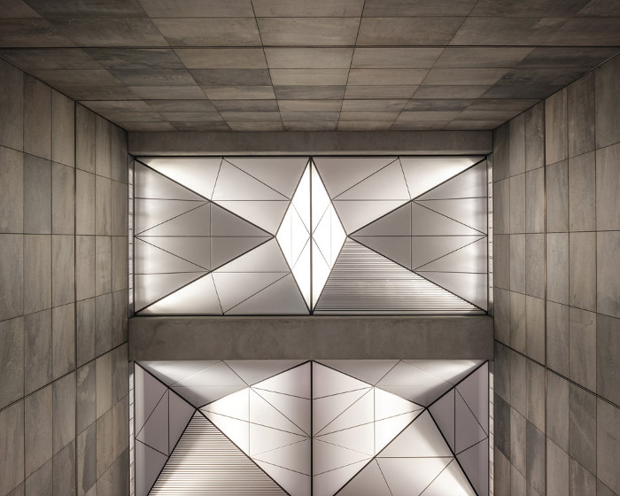 Where skylights don't exist, uplights illuminate the origami-folded ceiling that disperses light throughout the station. Image credit: Coast / Rasmus Hjortshøj