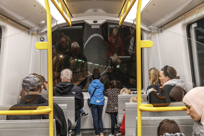 Children stand at the front of the driverless trains, looking out into the tunnel. Image credit: Coast / Rasmus Hjortshøj.