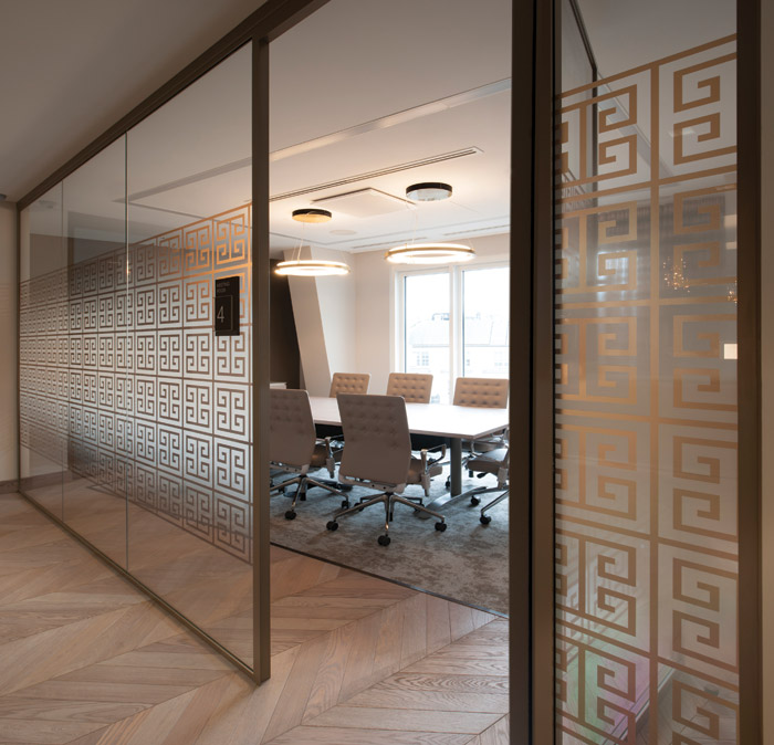 Greek-pattern graphics adorn this glass partition, with a room booking system sitting on the partition