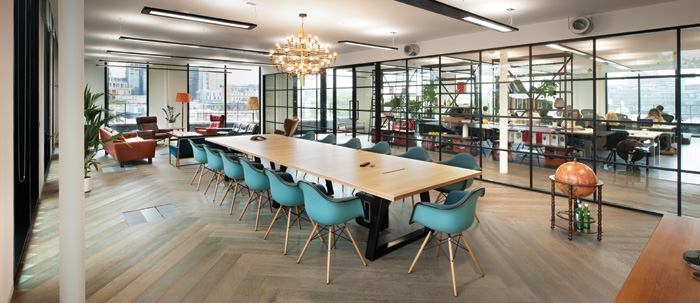 A meeting room has an open-plan feel thanks to the whole wall as transparent partitioning
