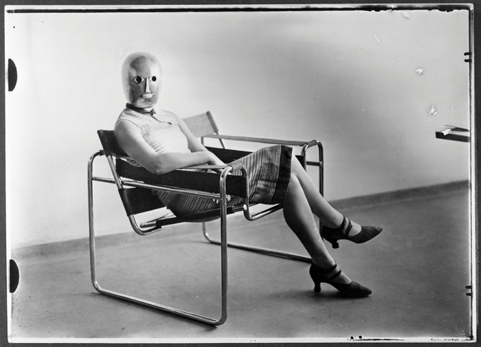 A woman in a mask by Oskar Schlemmer and a skirt made from material designed by Elisabeth Beyer-Vogler, sits in a Marcel Breuer chair