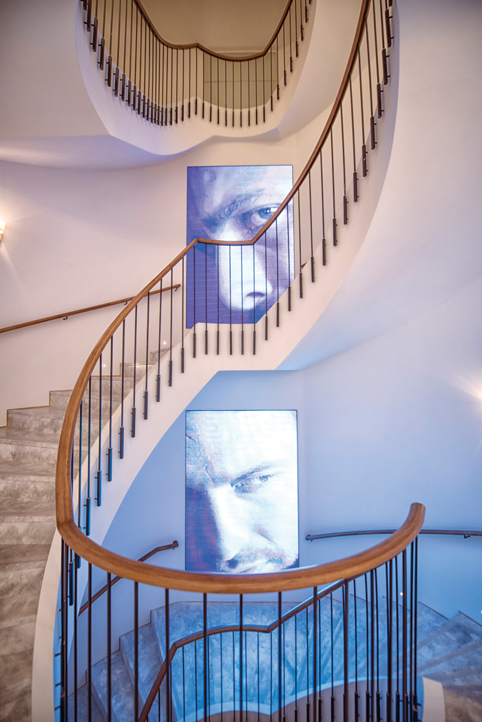 A wide spiral staircase of marble lined with digital screens links the floors