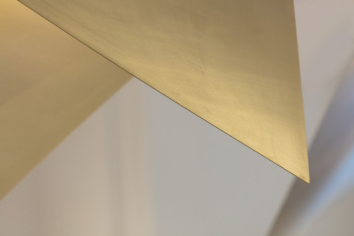 Folded brass details in the interior include the bespoke pendant lights, designed by Kinnersley Kent Design, and hanging rails and hooks. The use of brass references the brass zips and fasteners used the clothing line