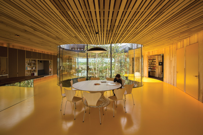 Maggie's in Oldham, designed by dRMM, has a mature tree at its heart, and uses timber throughout. It is the first cross-laminated hardwood building in the world, with an exterior of corrugated, heat-treated American tulipwood. Image Credit: Alex De Rijke