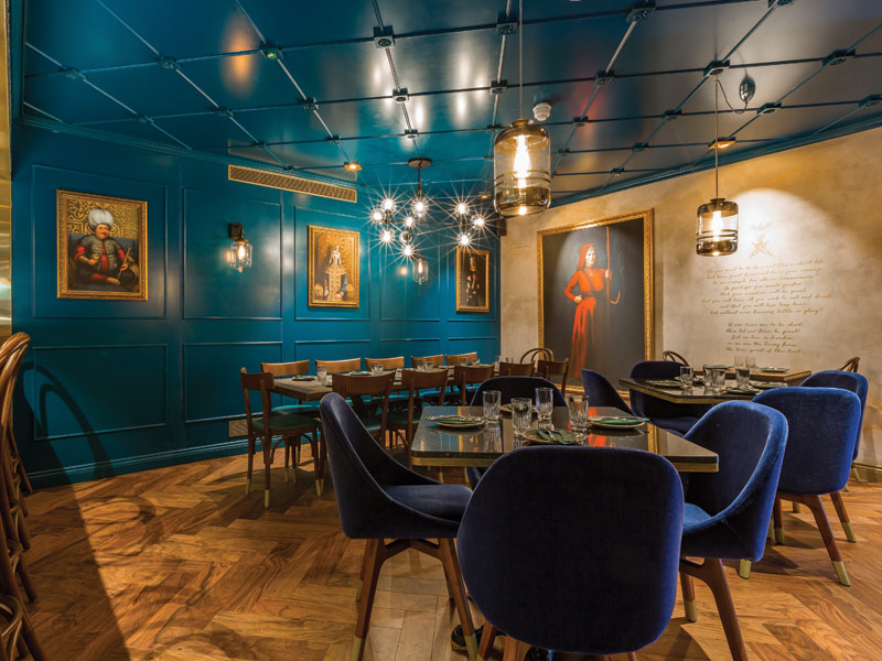 Turquoise wall and ceiling panels are mixed with gold, brass and oak for a warm ambience