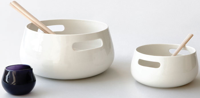 Kolmikko - The salad bowl set comprises a large porcelain bowl for salad, smaller porcelain bowl for side dishes, a small glass jug for salad dressing and wooden utensils. The bowls have handles for ease of carrying or serving, with the design inspired by the act of sharing. Designed as a stackable set of 'long-lasting household items' it forms the studio's first product made by craftsmen in Finland.