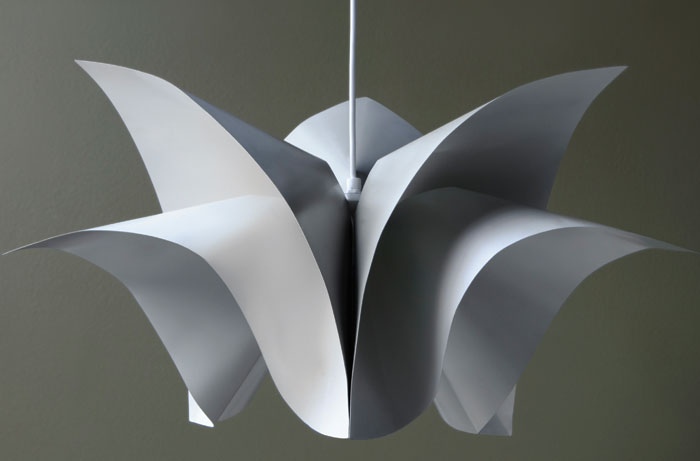 Flora - This pendant luminaire features three identical modules, bent from sheet steel to create a complex, sculptural fixture. 'The inspiration started from folding paper into interesting shapes and testing how to combine that with the sturdiness of metal,' explains Uski. Available in different sizes, Flora also creates a dramatic feature when hung in multiples.